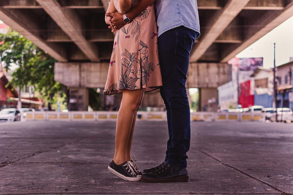 Fotografia dos pés do casal. Casal abraçado. composição da foto: corte da fotografia na cintura do casal. Ensaio realizado na rua. Terceira Ponte, Vila Velha,ES.