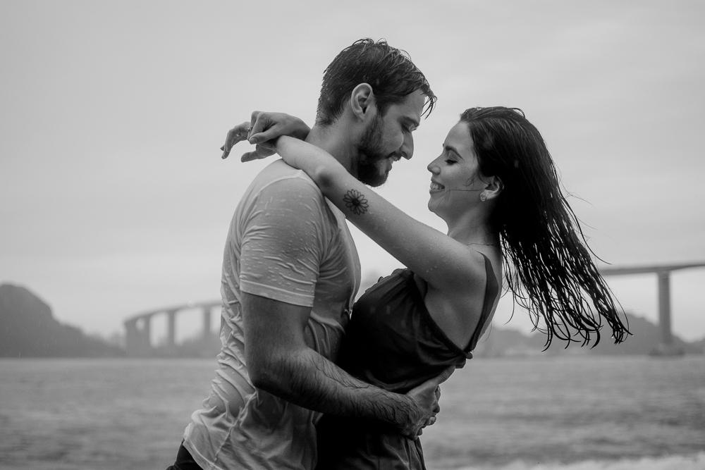 Fotografia preto e branco do casal na chuva. Composição de fundo a terceira ponte de vitória. Capital do Espírito Santo.