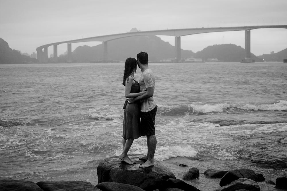 Retrato preto e branco do casal olhando para terceira ponte de vitória, ES. Casal em pé na pedra, próximo ao mar.