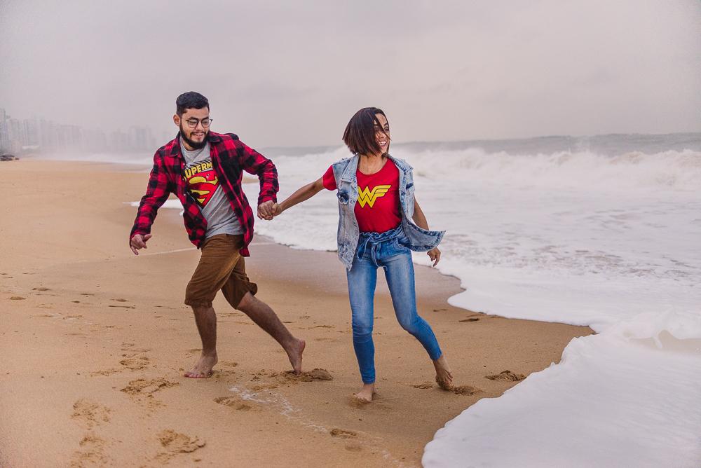 Fotografia do casal correndo das ondas e espumas que se forma na areia ao quebrar das ondas. Praia de Itaparica, Vila Velha, ES.