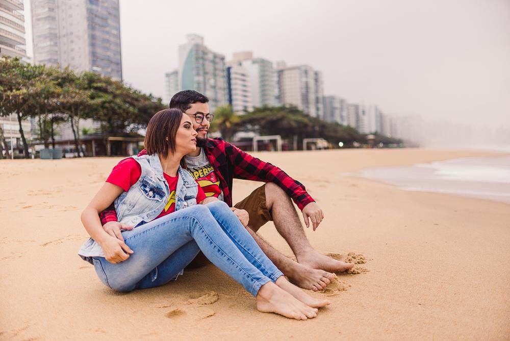 Fotografia de Casal sentando na areia, apreciando o mar, num dia nublado. Praia de Itaparica, Vila Velha, ES.