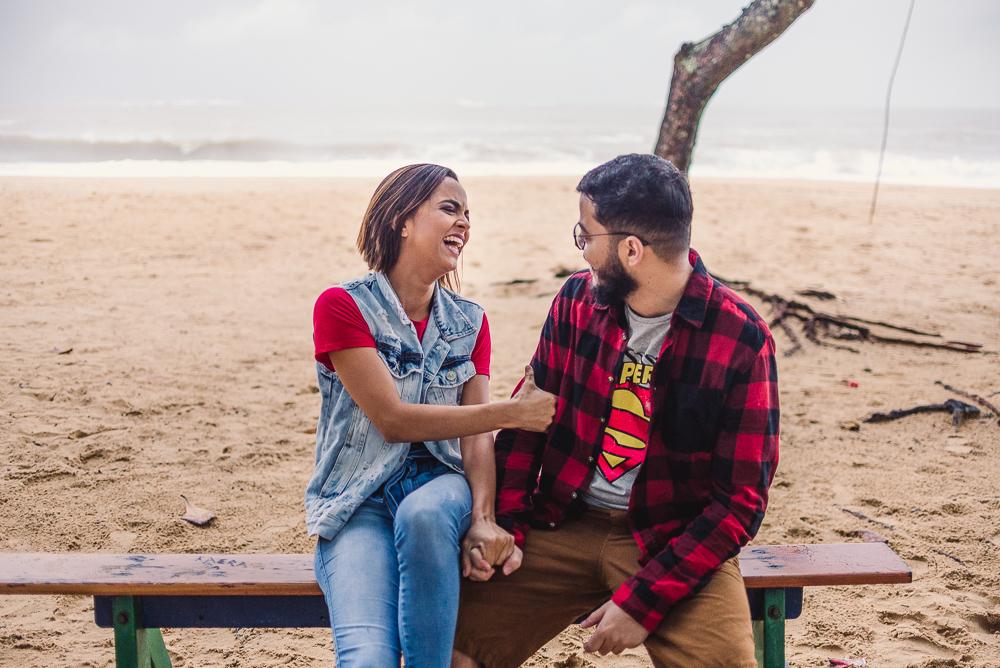 Fotografia do casal gargalhando, sentados no banco do parquinho na Praia de Itaparica, Vila Velha, ES.