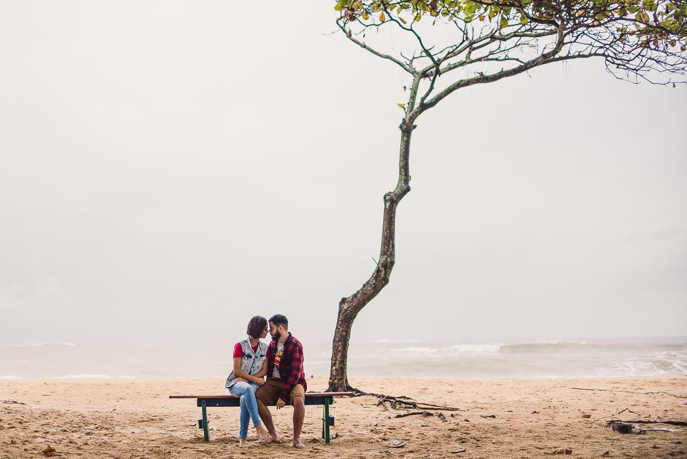Retrato feito de longe, do casal sentado no banquinho do parquinho da Praia de Itaparica. Ao fundo uma arvore  com folhagens altas, tronco fino e longo. Ao fundo o mar. Dia nublado, pela manhã.