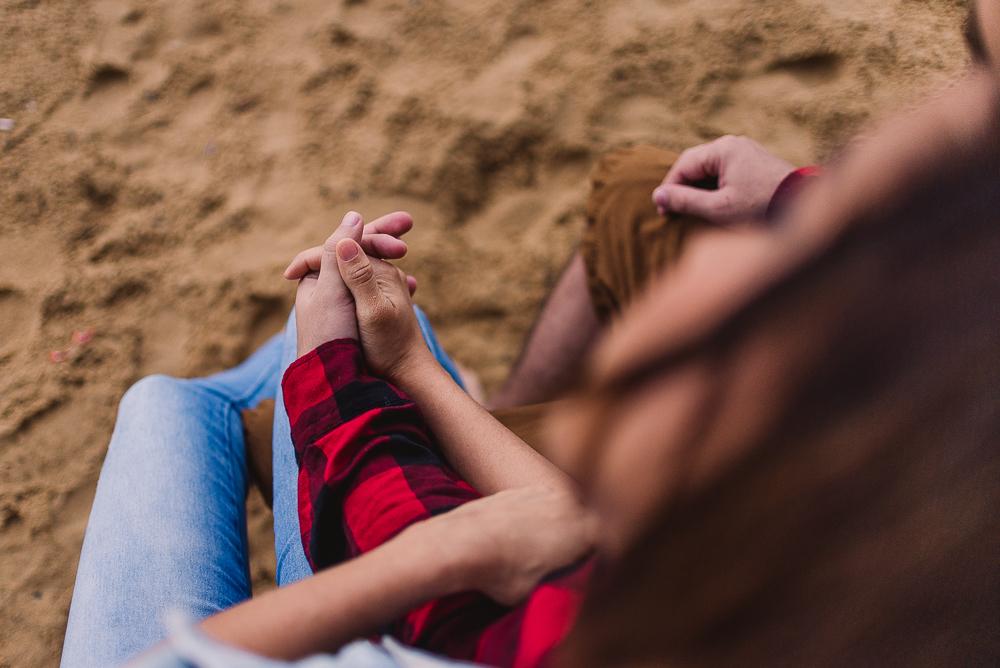 Fotografia do casal de mãos dadas, sentado na banco da praia, com os pés na areia. Ensaio fotográfico realizado na Praia de Itaparica, Vila Velha, ES.