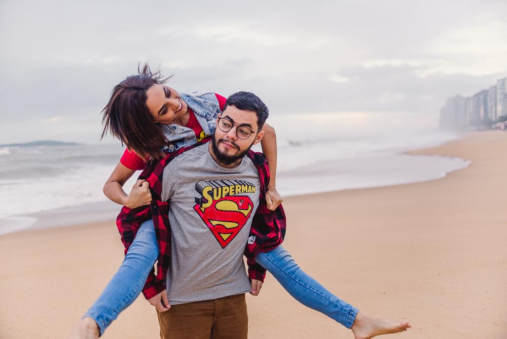 Mulher sendo carregada nas costas pelo homem. Fotografia de ensaio de casal realizada na praia de itaparica.
