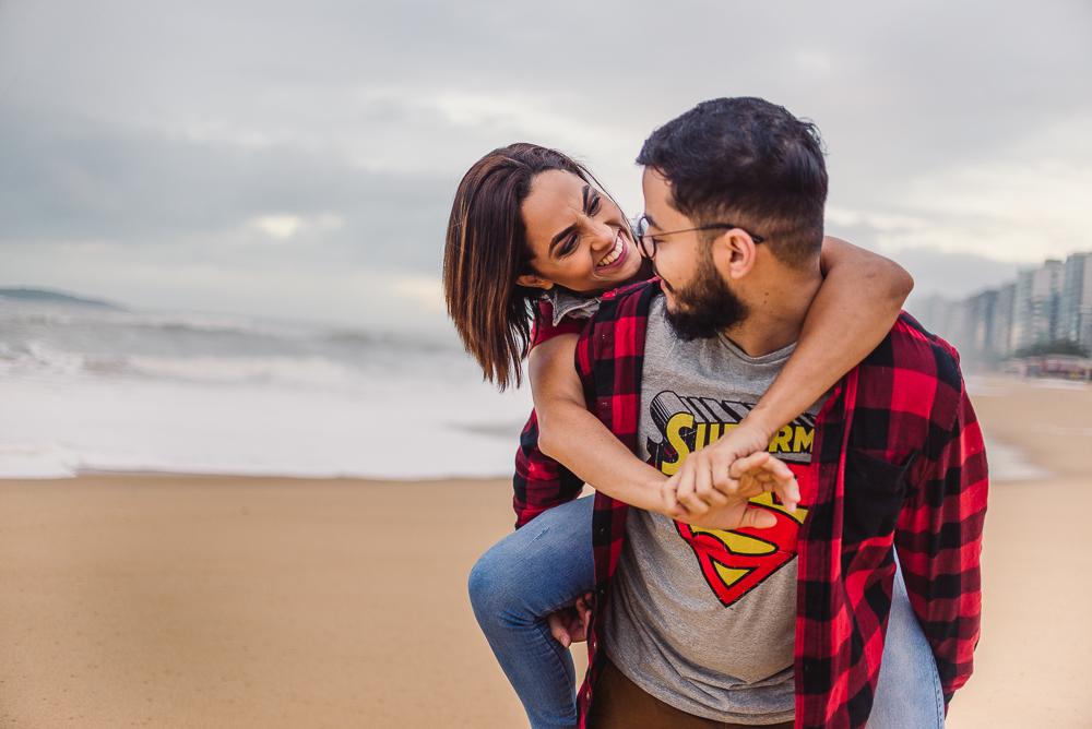 Mulher sorrindo para o parceiro, enquanto ele a carrega nas costas. Fotografia de Ensaio Casal. Praia de Itaparica - Vila Vela - ES.