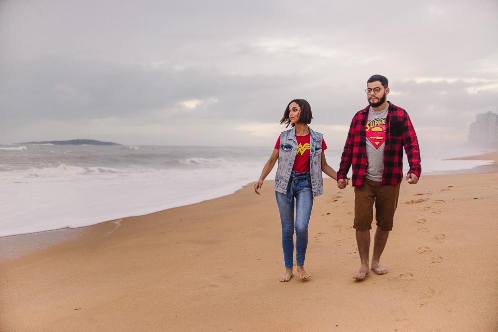 Casal de mãos dadas, andando sobre areia da praia, olhando para o mar. Ensaio fotográfico de casal. Praia de Itaparica, Vila Velha ES.
