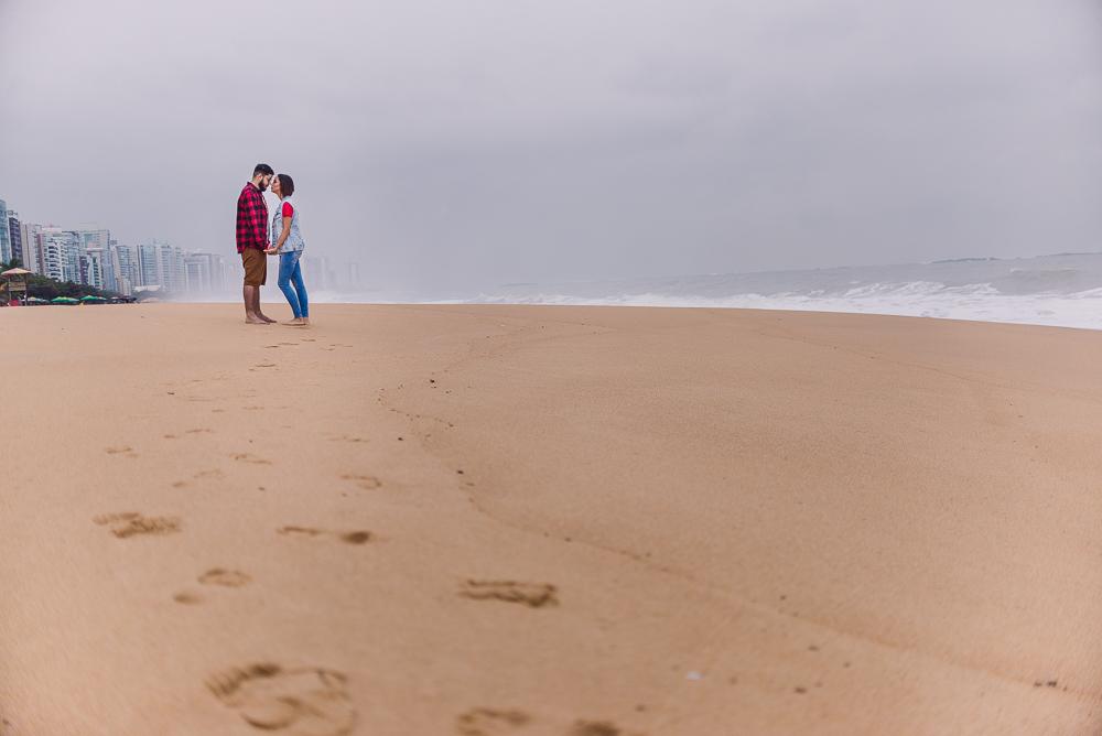 Pegadas do casal na areia da praia de itaparica. Casal de frente para o outro no fundo da composição da foto. No horizonte, céu nublado e prédios da orla da praia de Itaparica.