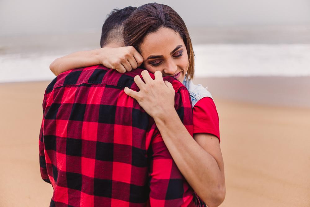 Casal abraçado. Ele de Costas e ela de frente para câmera. Sorrindo e de olhos fechados. Abraço forte. Fotografia de Ensaio do casal na Praia de Itaparica, Vila Velha, ES