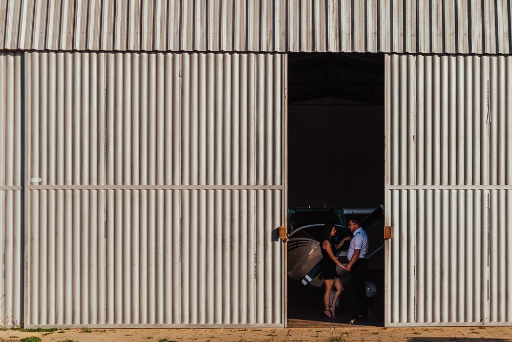 Ensaio Fotográfico de casal no aeroporto. Fotografia do casal no portal do hangar.