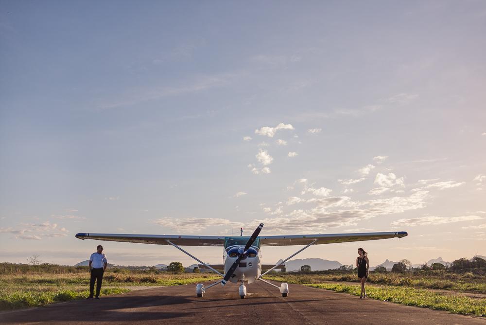 Casal e avião na pista de pouso do aeroporto. Debaixo das asas do avião.