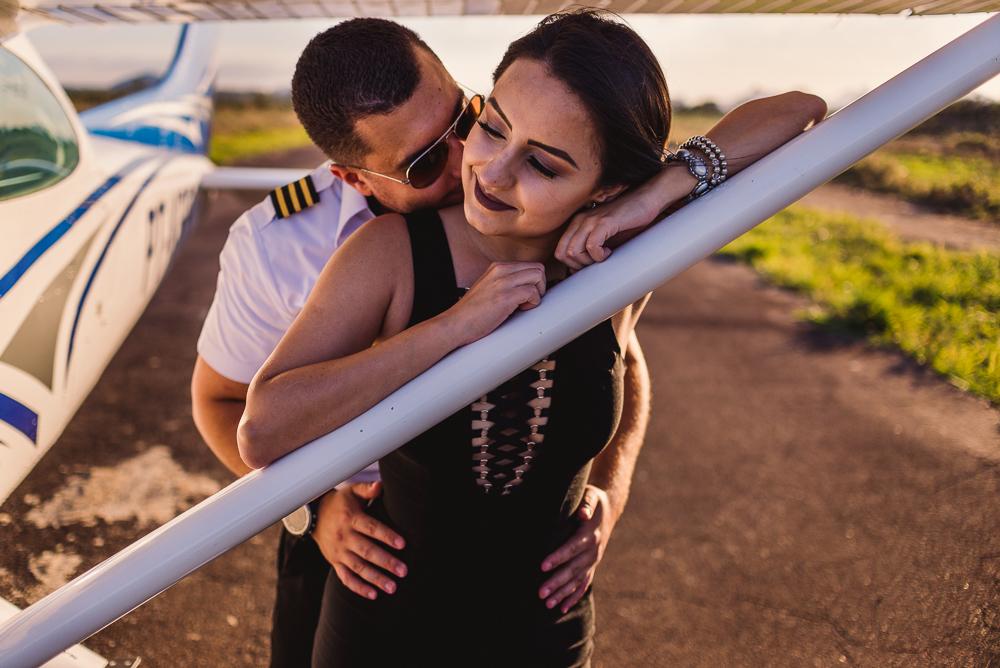 Ensaio fotográfico. Noivo abraçando noiva que está apoiada na asa do avião.
