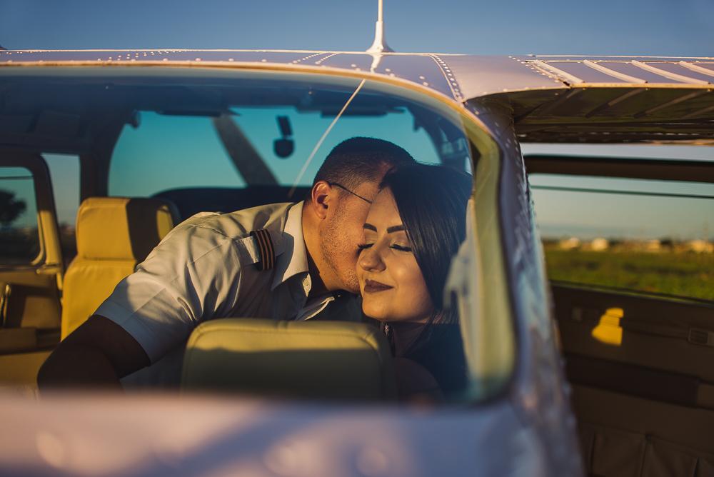 Ensaio fotográfico do Casal dentro do avião. Noivo dando um beijo no rosto da noiva.