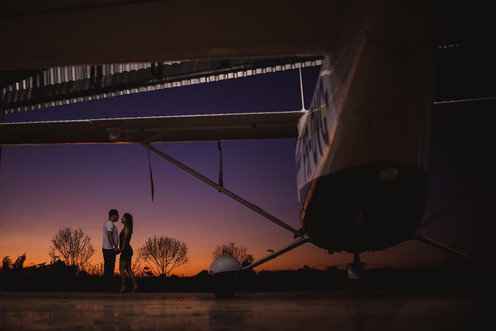 Fotografia do fim do ensaio no hangar do aeroporto. Por do sol bem baixo com vegetações distantes. Casal de mãos dadas de frente um para o outro. Fotografia silhueta.