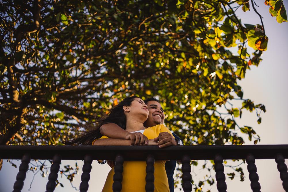 Casal debruçado e sorrindo. Olhando o horizonte. Fotografia feita no Farol de Santa Lúcia em Vila Velha, ES.