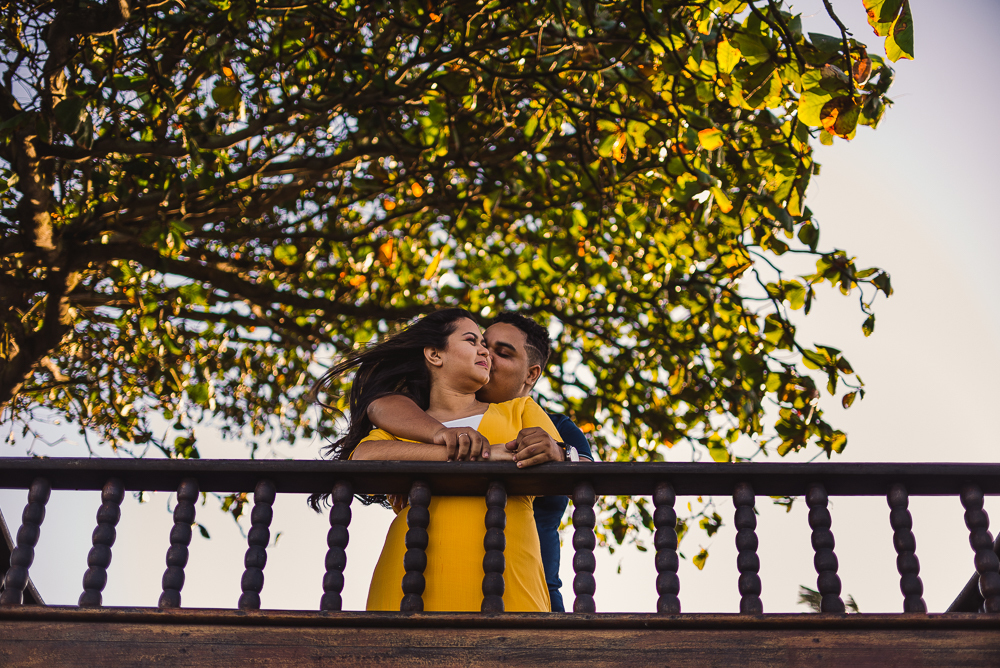 Fotografia no Farol de Santa Lúcia, Vila Velha, ES. Noivo beijando o rosto da noiva. Estão apoiados no beiral do deck.