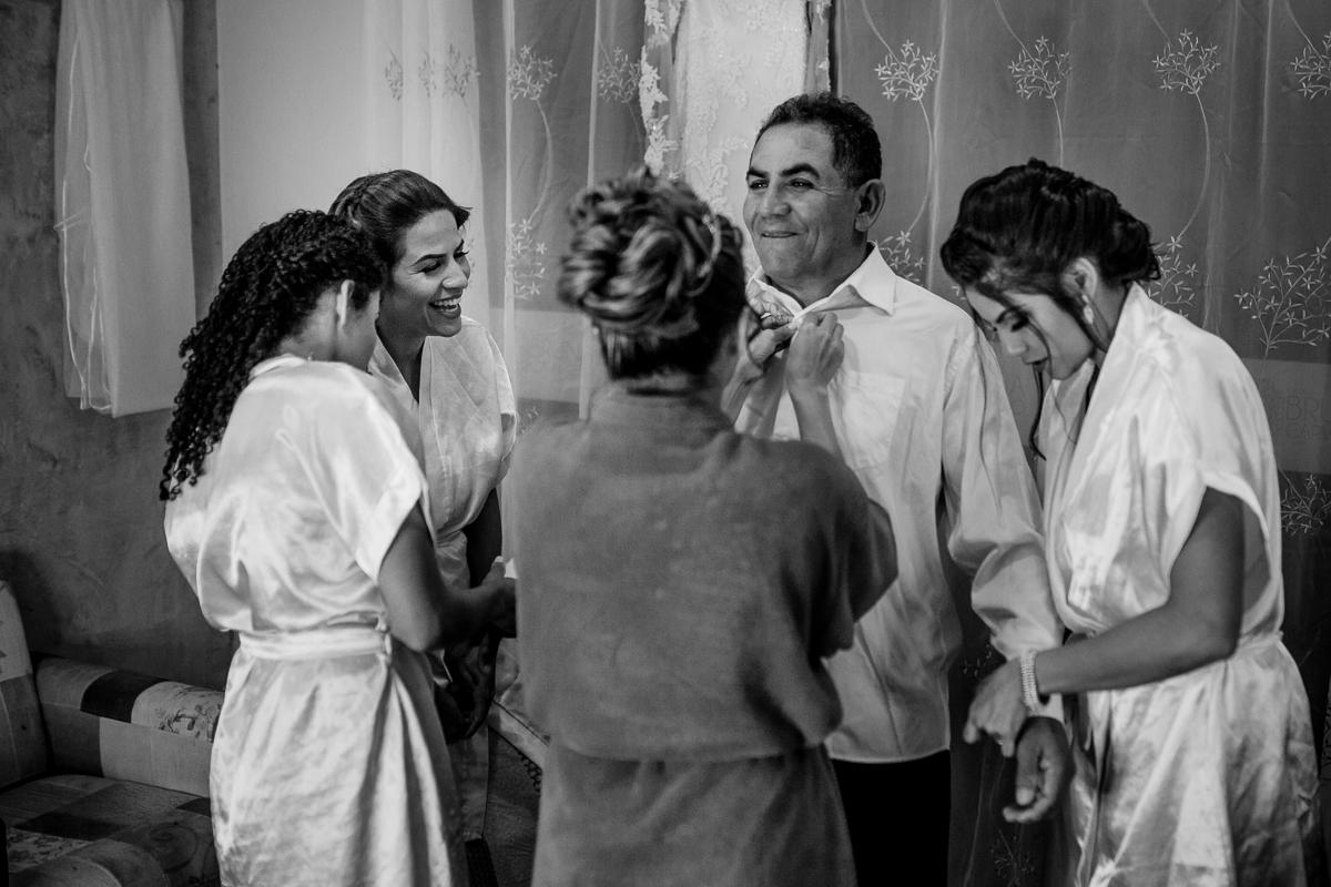 Fotografia da Noiva e suas irmãs arrumando o pai para cerimônia de casamento.