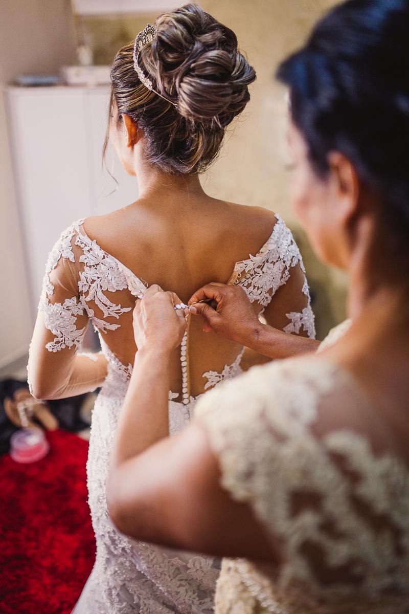 Mãe abotoando o vestido da noiva. Making-of da noiva no Espaço Bruna Carvalho.