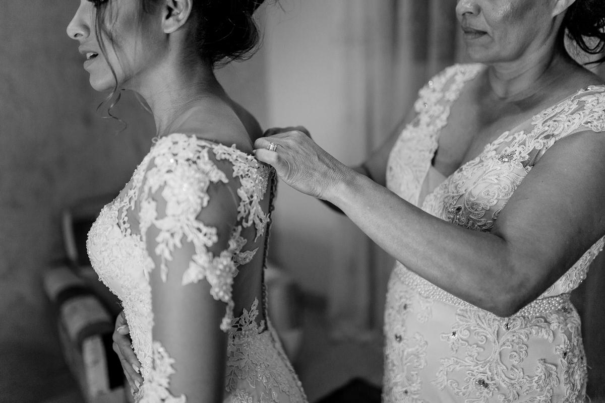 Fotografia da mãe abotoando vestido da noiva. Making-of da noiva. Espaço Bruna Carvalho, Vila Velha - ES.