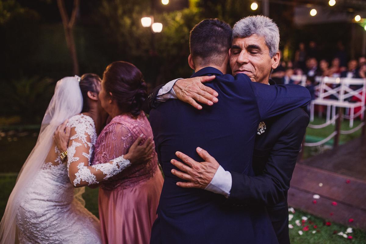 Fotografia dos noivos abraçando os pais do noivo. Num momento de entrega do casal.