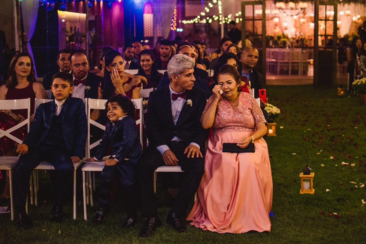 Fotografia de casamento. Mãe do noivo chorando. Fotografia dos convidados assistindo a cerimônia de casamento.