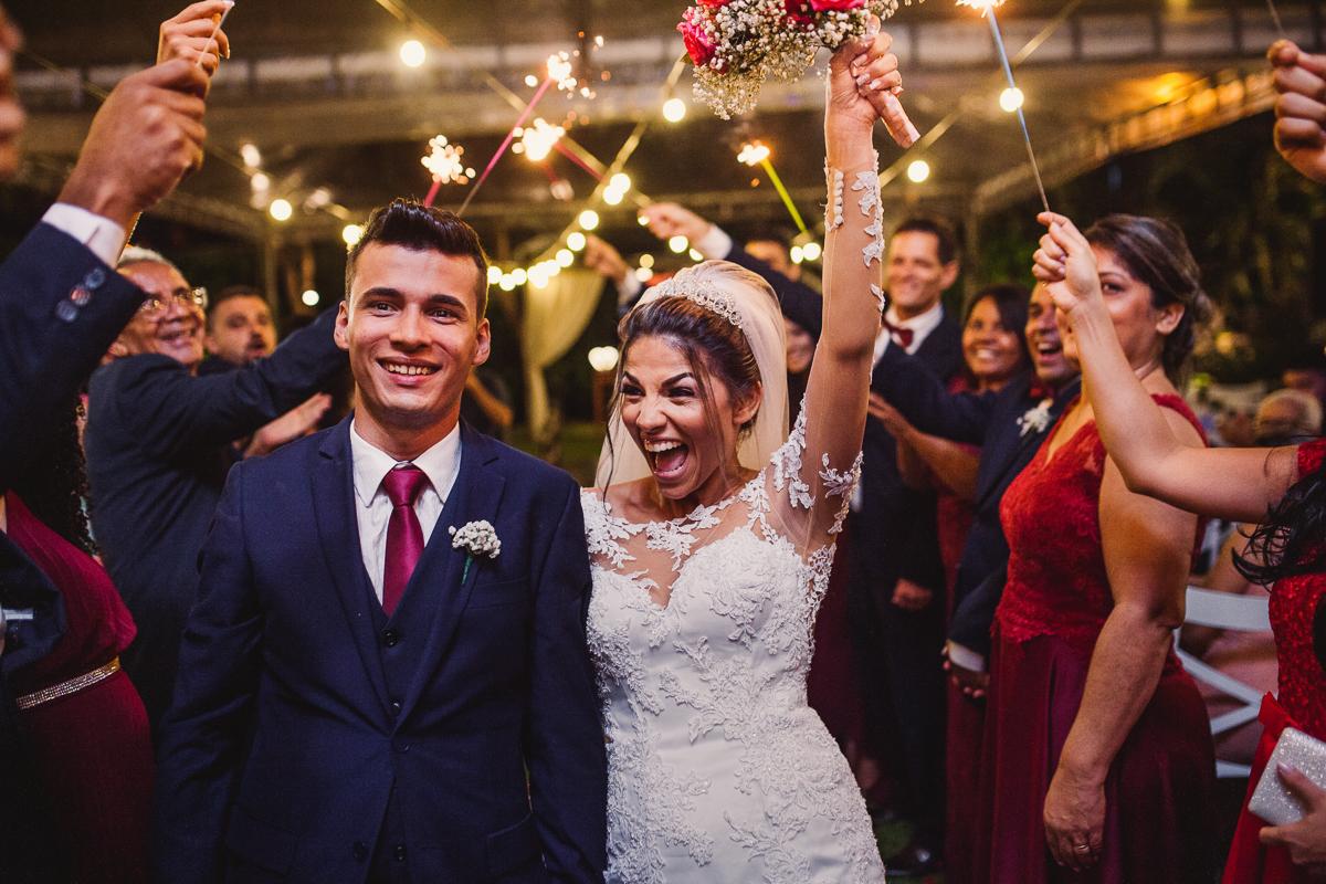 Fotografia da saída dos noivos pelo corredor, comemorando realização. Noiva com as mãos para cima, segurando o buquê.