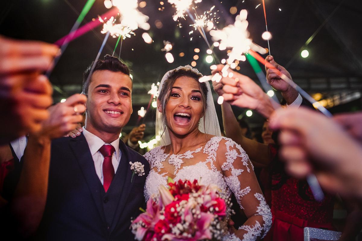 Fotografia dos noivos na saída da cerimônia. Momento de felicidade e confraternização. Casamento no Cerimonial Saron em Vila Velha.