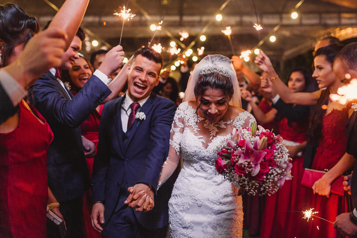 Noivo rindo na saída do casal ao terminar a cerimônia de casamento.