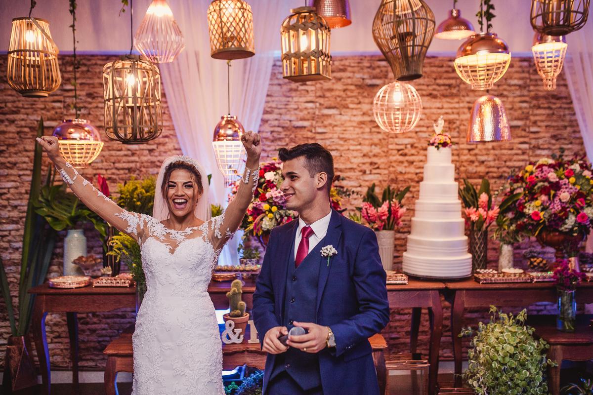 Fotografia da noiva comemorando cerimônia em frente a mesa ornamentada. Fotografia de casamento no Cerimonial Saron, Vila Velha, ES.