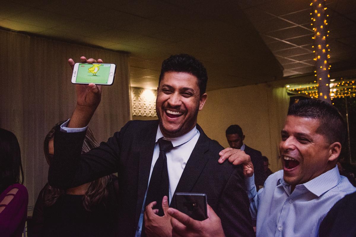 Convidado segurando o celular, mostrando vídeo de criança. Uma tática para tirar fotos de crianças e deixa-las concentradas na foto. Casamento realizado no cerimonal saron.