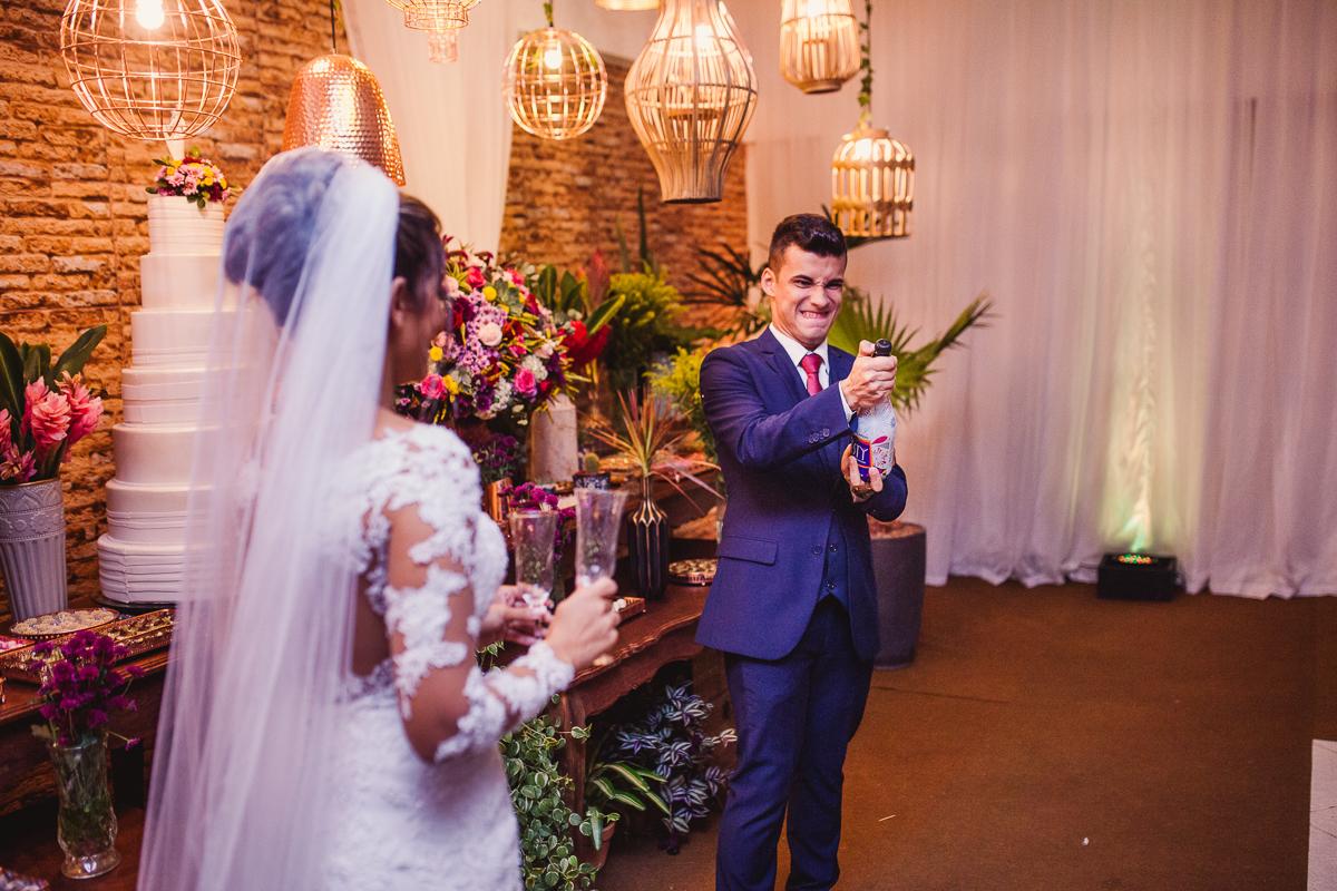 Noivo estourando champanhe. Fotografia de casamento. Cerimonial Saron Vila Velha, ES.