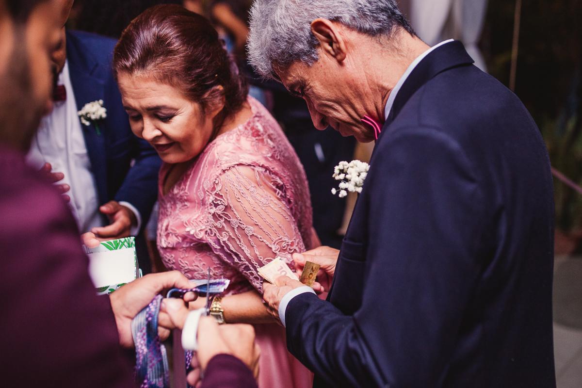 Pai do noivo contando dinheiro para dar para o recem casado. Fotografia de casamento. Cerimonial Saron. Vila Velha Es.