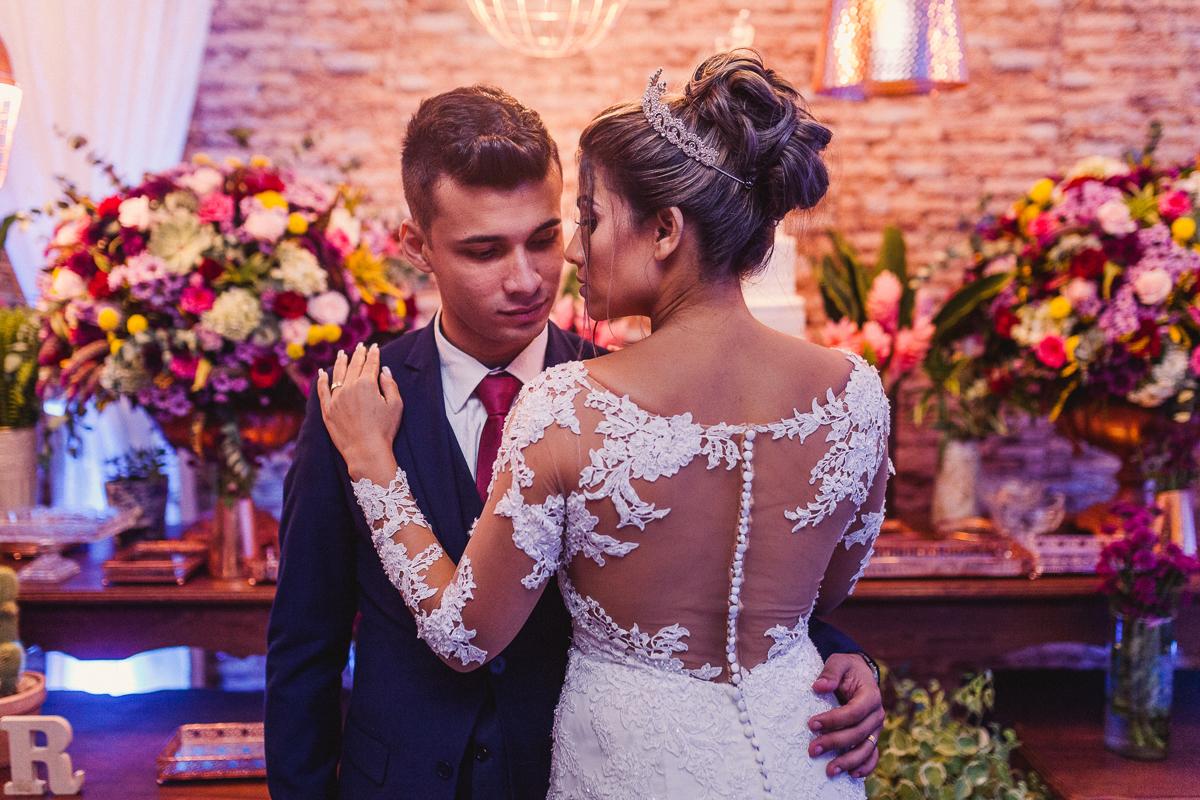 Retrato do casal abraçado. Mostrando as costas do vestido da noiva. Noiva apoiando sua mão no ombro do noivo. Noivo olhando para noiva. Noiva com seu olhar direcionado para seu ombro. Fotografia de casamento realizada no Cerimonial Saron. Vila Velha, ES.