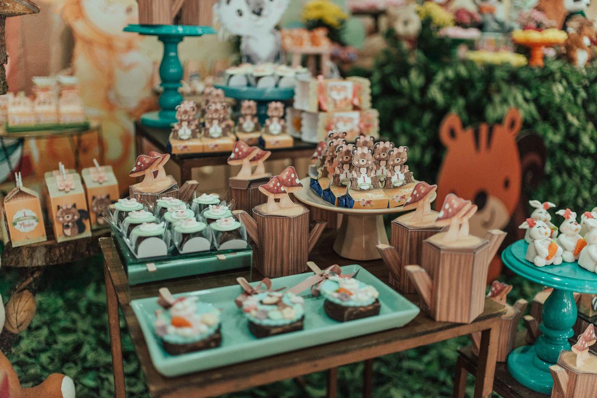 Foto da mesa decorada com doces e cupcakes da festa de aniversário de 1 ano.
