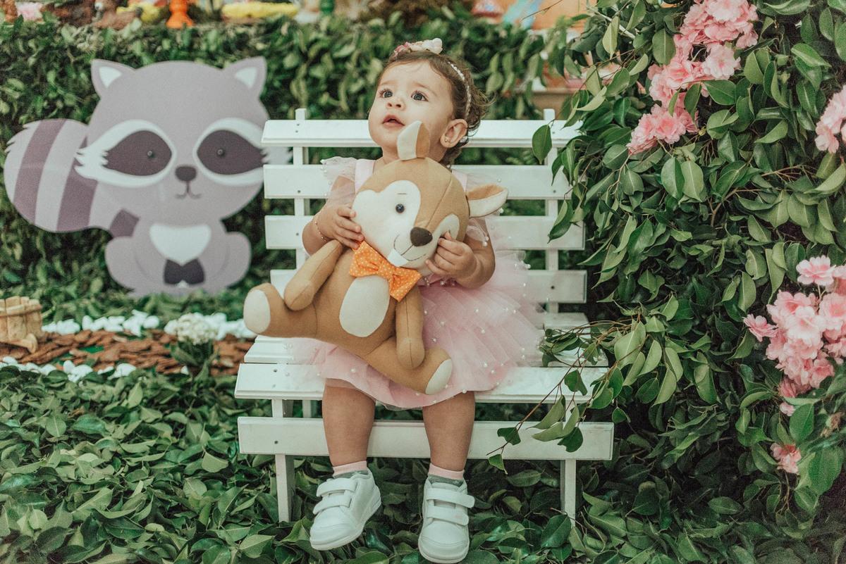 Fotografia da aniversariante sentada no banquinho do bosque (decoração da festa), segurando urso de pelúcia.