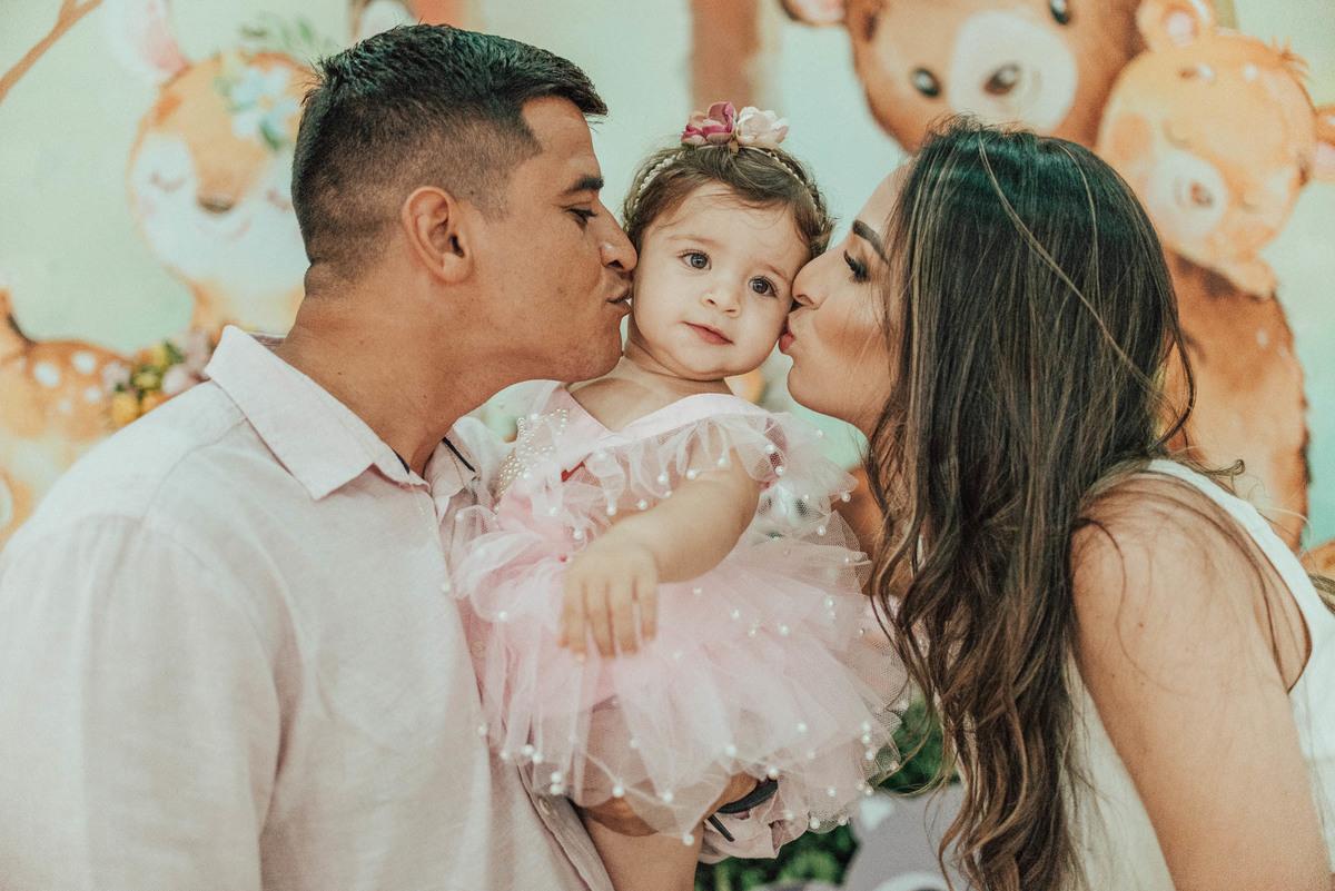 Fotografia dos pais beijando a filhinha que está completando um aninho.