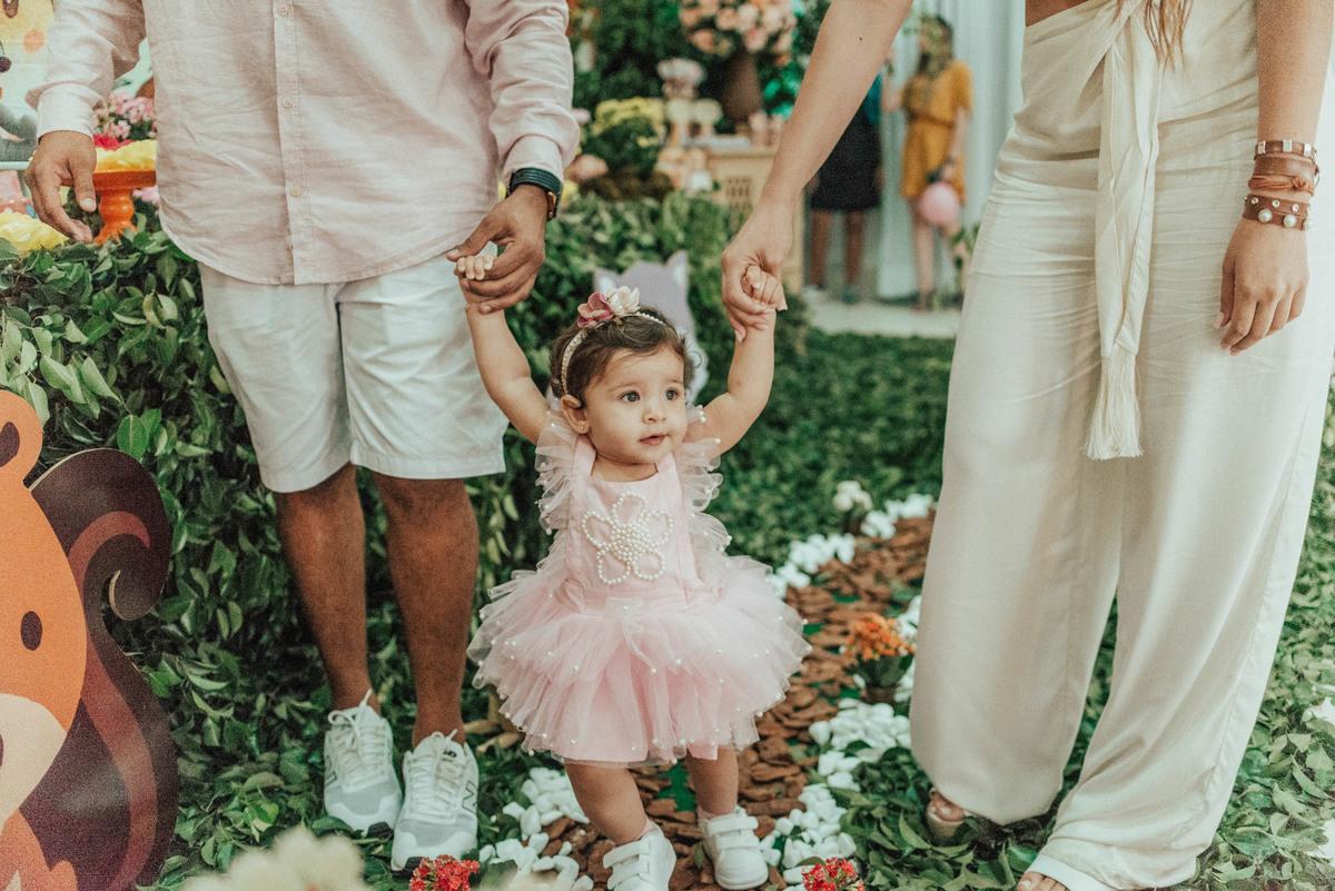 Pais de mãos dadas com a filha, passeando pela festa.