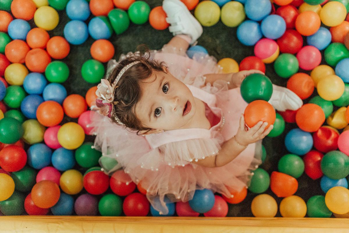 Retrato da aniversariante, visão de cima, sentada na piscina de bolinha.