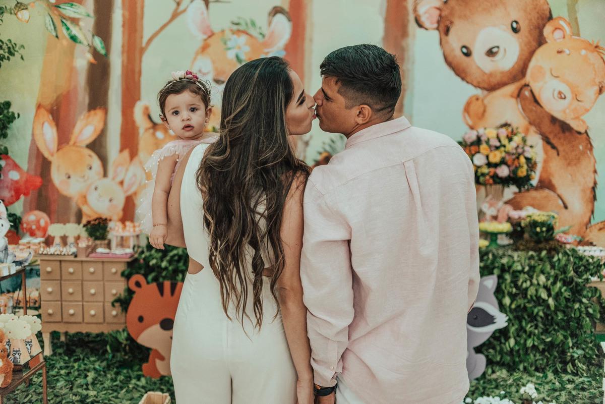 Pais de costas e mãos dadas, se beijando. Filha nos braços da mãe, olhando para a câmera.