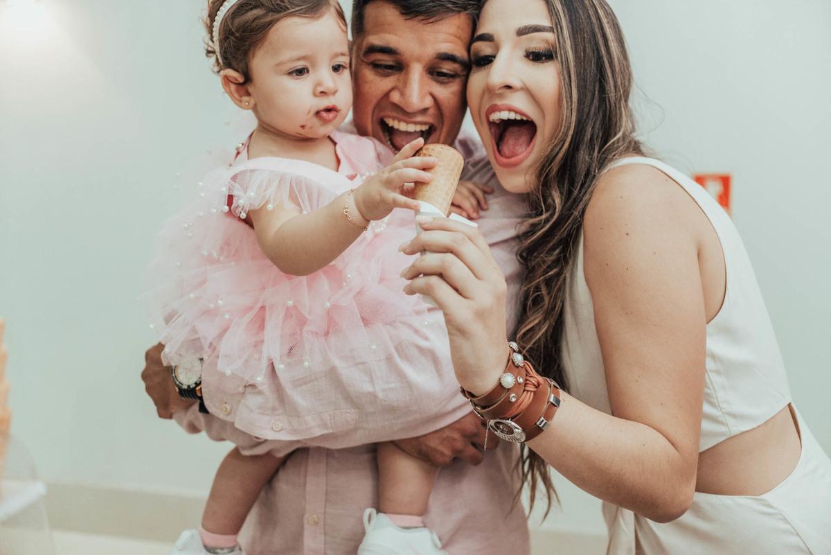Família com filha no colo comendo casquinha de sorvete, bem sorridentes.