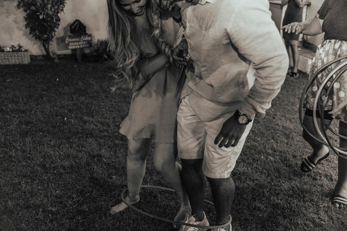 Fotografia da brincadeira que rolou na festa. Brincadeira de criança para adultos. Casal disputando bambolê no chão.
