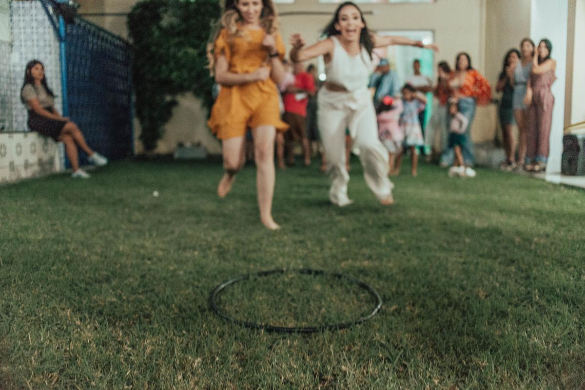 Irmãs adultas correndo para disputar o único bambolê no chão. Fotografia da Brincadeira de adultos que rolou na festa de aniversário de 1 ano.