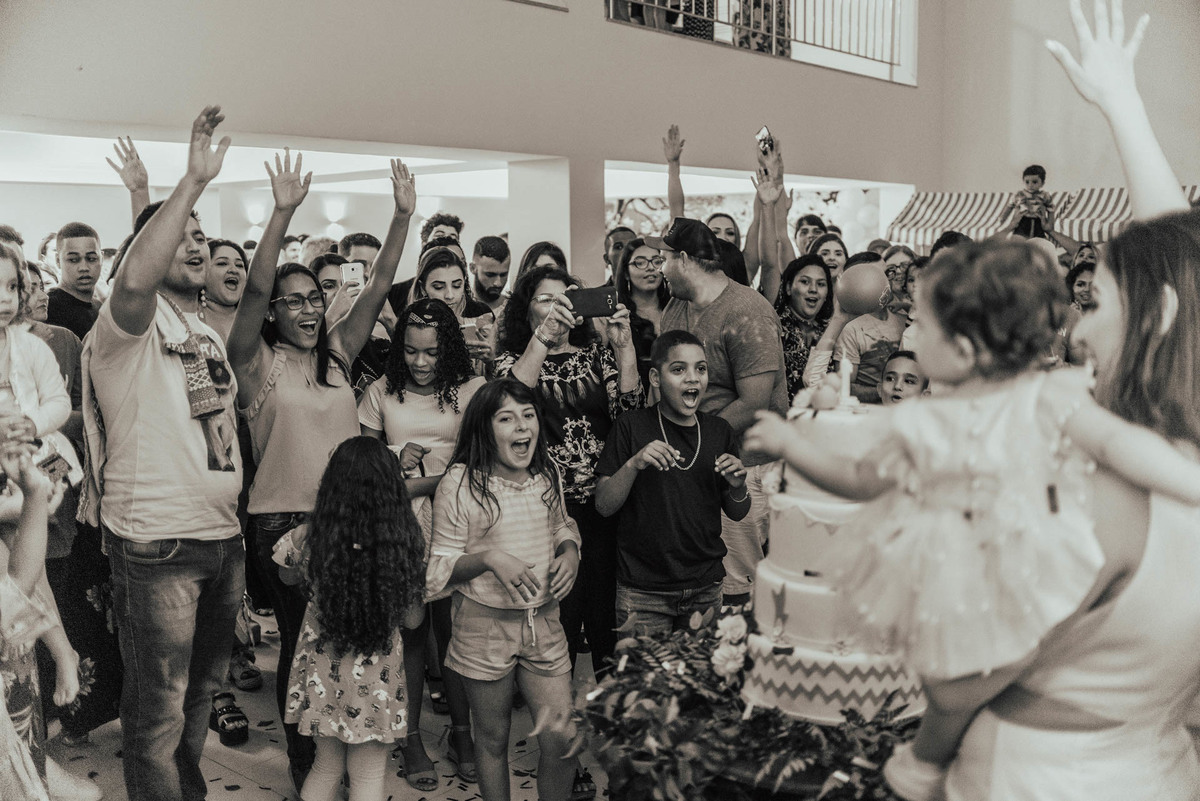 Todos os convidados com as mãos para cima, comemorando os parabéns que foi cantando anteriormente, na festa de aniversário de 1 aninho.