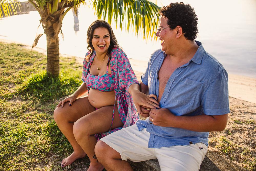 Casal gargalhando, sentado no banco da praça do farol na ilha de Paquetá, Rio de Janeiro.