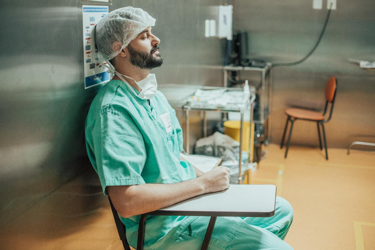 Fotografia documental de parto. Pai sentando na sala de cirurgia com olhos fechados. Tenso e aguardando a cirurgia de parto.