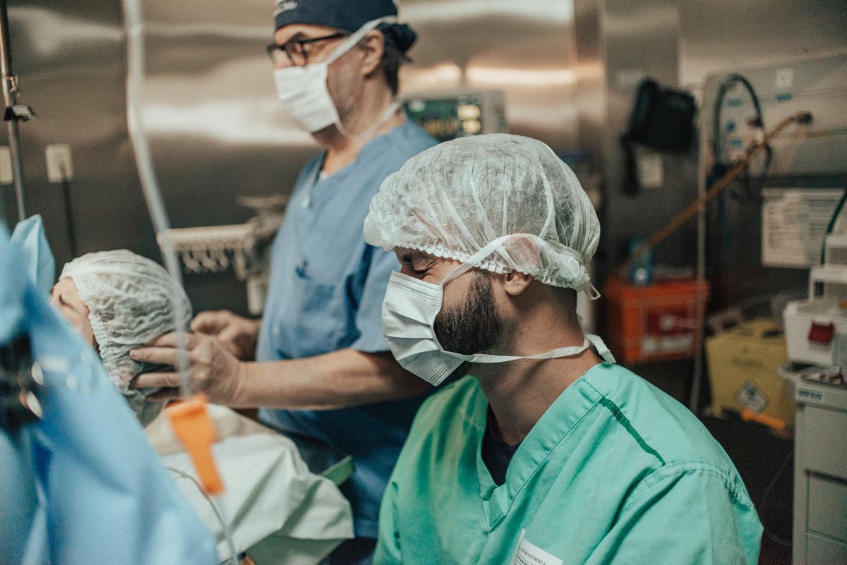 Fotografia do pai emocionado ao ver sua filha pela primeira vez. Fotografia Documental de Parto realizada no Hospital Vitória Apart, Serra, ES.