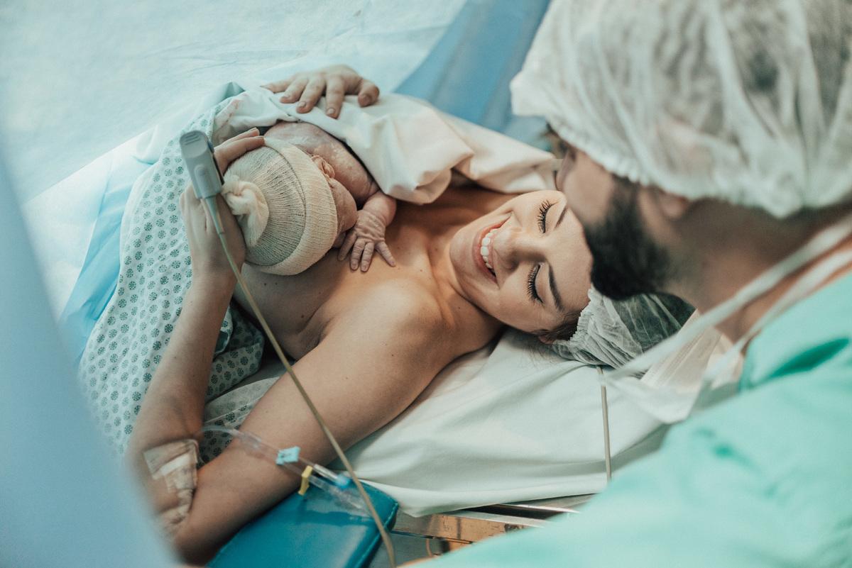 Documental de parto. Mãe olhando para filha que está no seus braços. Deitada na mesa de cirurgia.