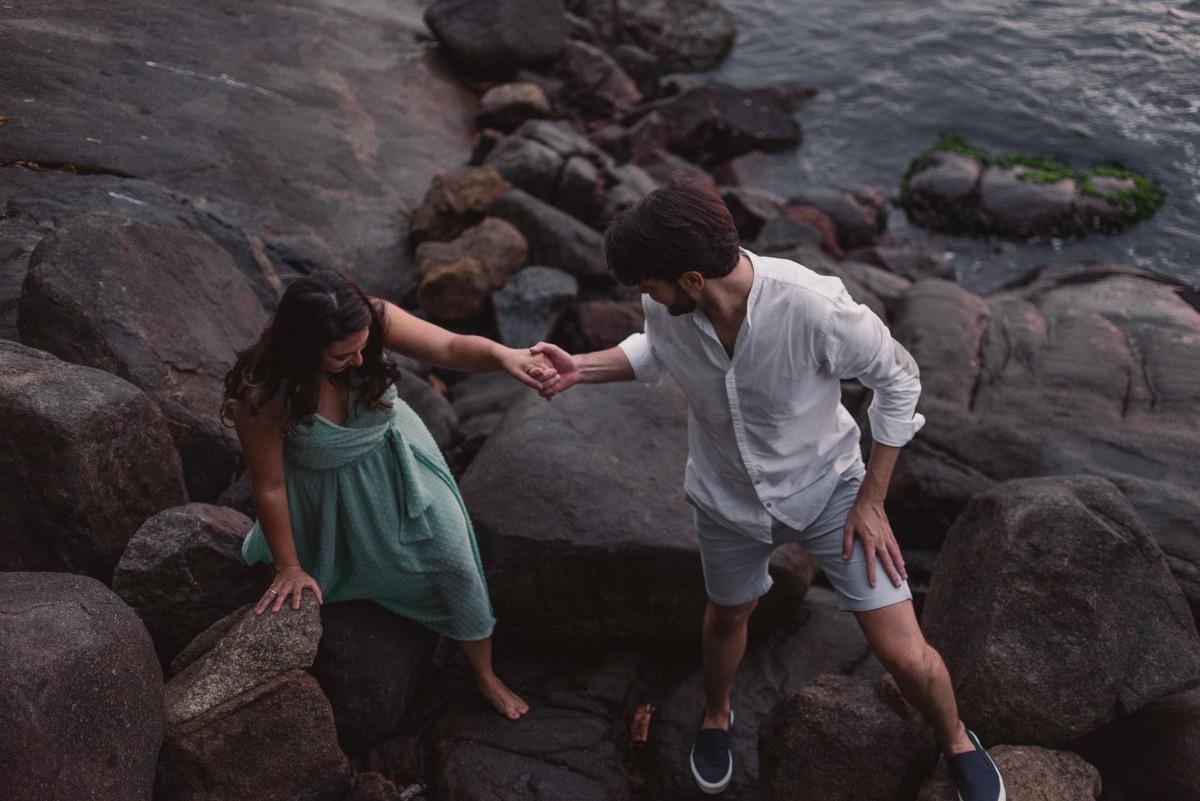 casal de maos dados ao atravessar as pedras da encosta da praia das bananas em vila velha espirito santo
