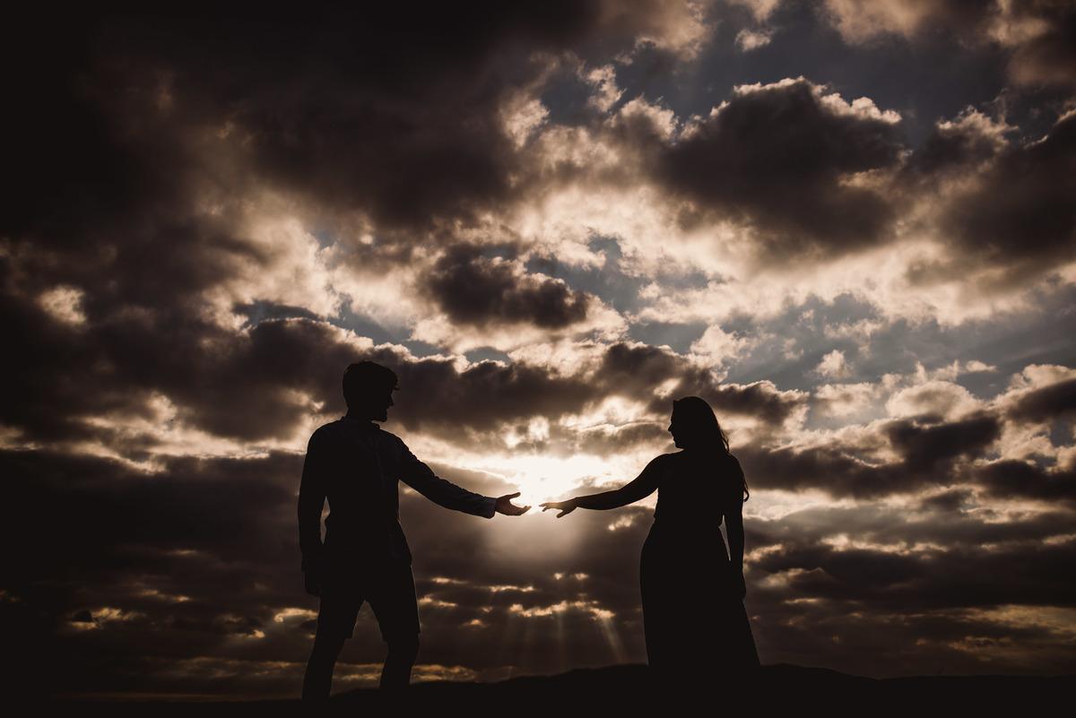 foto silhueta do casal na pedra da sereia em vila velha praia da costa