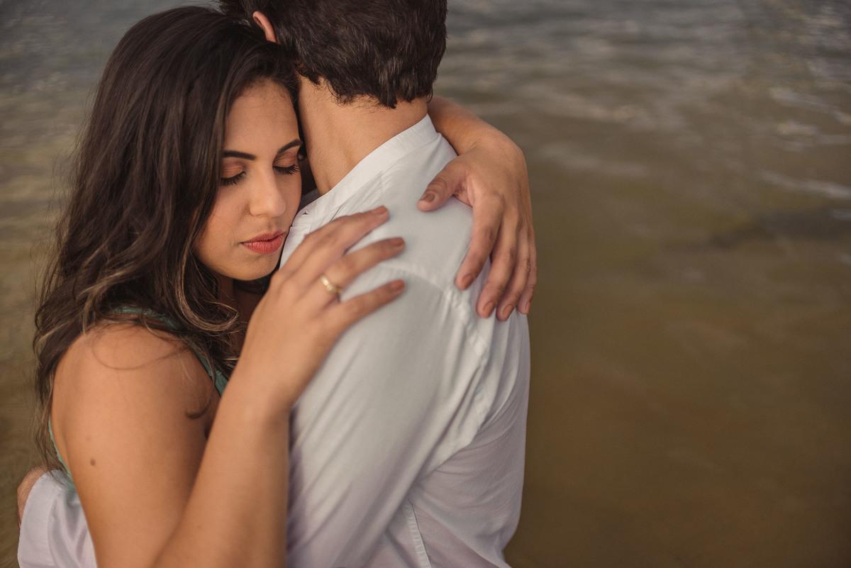 casal abraçado de olhos fechados dentro d'água na praia da costa